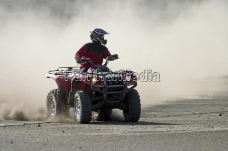 quad parte su una pista polverosa