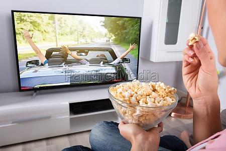 mano della persona che tiene popcorn