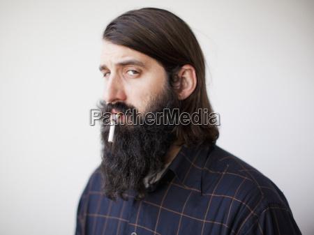 barbuto giovane con sigaretta rotta in