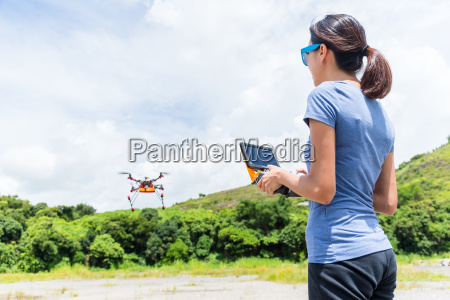 woman controlling flying drone