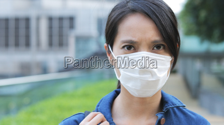 woman feeling sick and wearing face