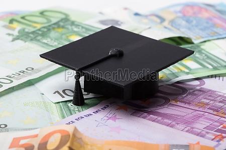tappo di laurea su banconote in