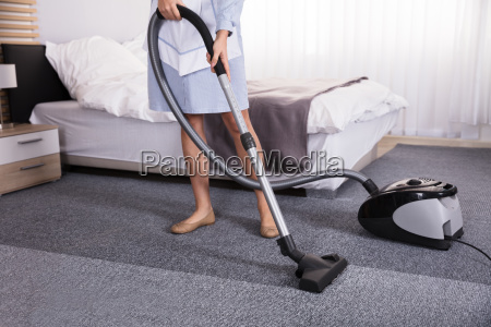 janitor using vacuum cleaner for cleaning