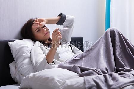donna malata che controlla la temperatura