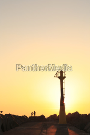 people and tower in the sunset