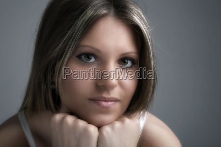 young woman trims her chin and