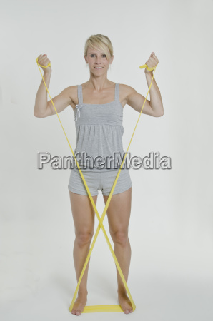 young woman holds yellow exercise band