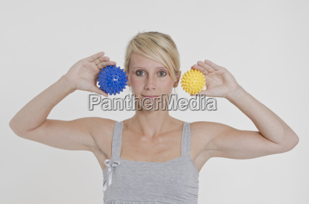 young woman holds 2 hedgehog balls