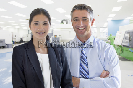 businessman and businesswoman in engineering factory