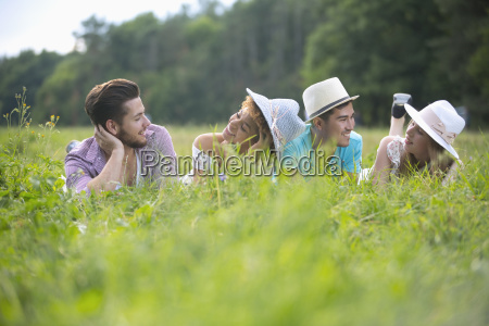young couples wearing hats lying in
