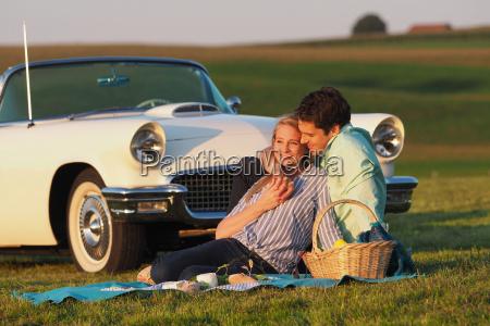 couple enjoying countryside picnic next to