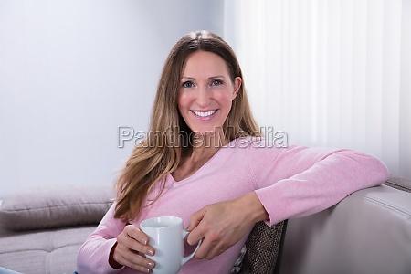 felice donna seduto su divano tenendo