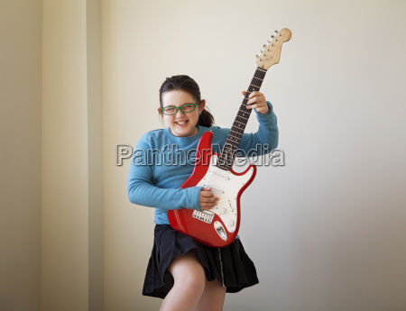 cheerful girl playing guitar against wall