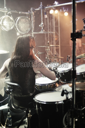 rear view of man playing drums