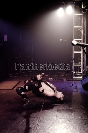 man performing stunt while playing guitar