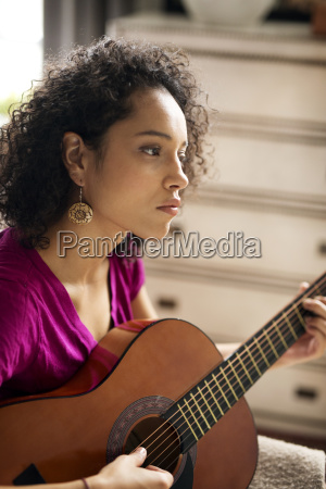 woman looking away while practicing guitar