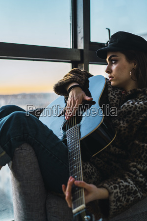 thoughtful young woman playing guitar while