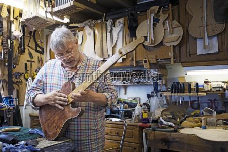 craftsman checking guitar while standing at