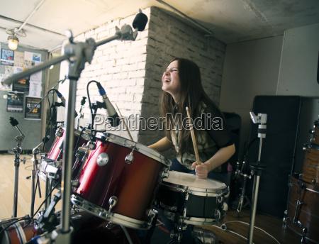 cheerful woman enjoying while playing drum