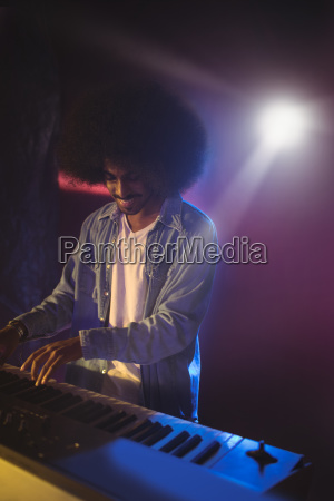 male musician playing piano on stage