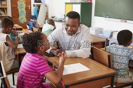 black male teacher helping elementary school