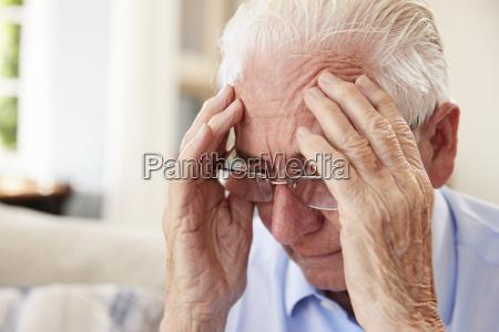anziano seduto sul divano a casa
