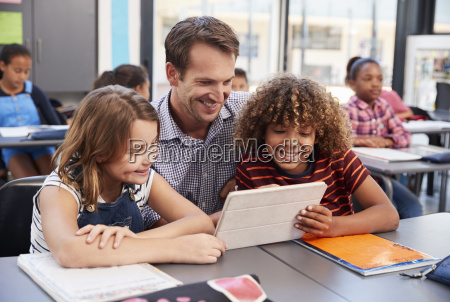 teacher using tablet with two pupils
