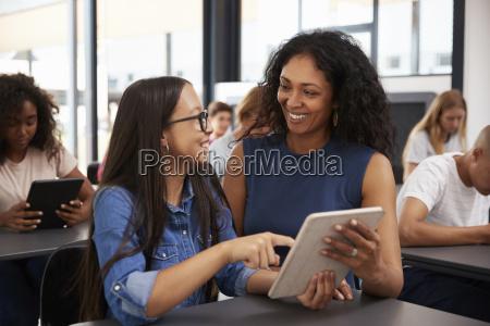 teacher helping teenage schoolgirl with tablet