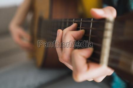 close up of woman playing guitar