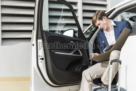businessman sitting in car with cell