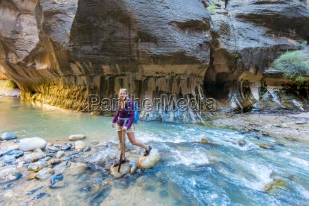 hiker crosses river on stones zion