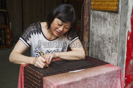donna che intaglia le iscrizioni sui