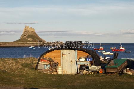barche ormeggiate nellacqua e un capannone