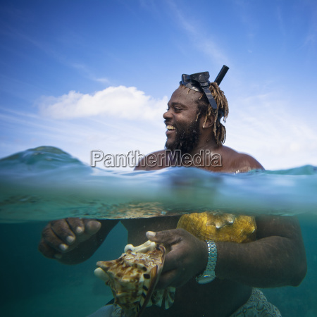 a man holds two large conch