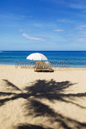 two beach chairs with umbrella on