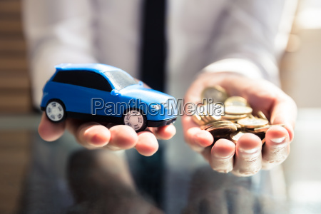 businessperson holding small blue car e