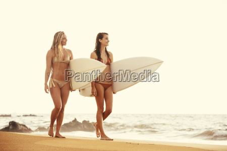 beautiful surfer girls walking on the