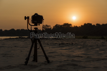 camera on tripod beside river at