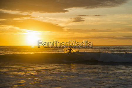 surfer riding a wave at sunset