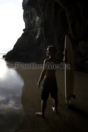 surfer at muriwai new zealand