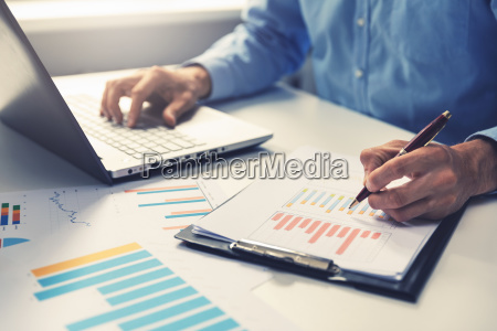 businessman analyzing annual business report with