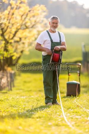 portrait of senior man gardening taking