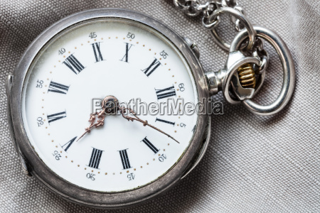 old pocket watch on gray textile