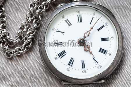 shabby silver pocket watch on gray