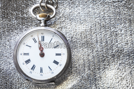 vintage pocket watch on silver fabric