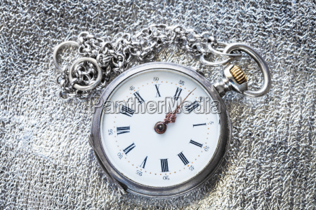 antique pocket watch on silver fabric