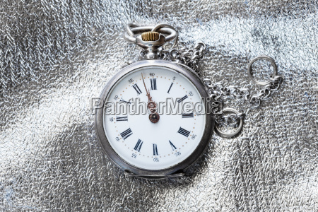 old pocket watch on silver fabric