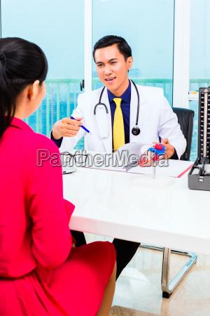 medico asiatico con paziente in chirurgia