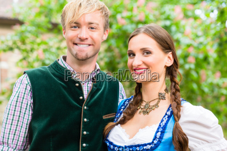 couple posing in bavarian clothes in