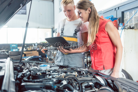 auto mechanic showing to a customer